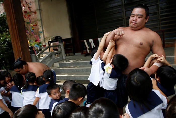Đô vật Kainoryu kéo các em bé lên bằng cánh tay của mình.