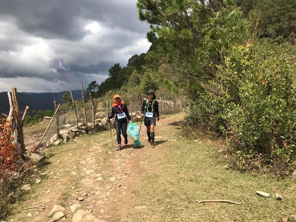 Hai VĐV Bùi Thị Thúy và Phan Phi tha bịch rác trên đường chạy. Ảnh: NVCC