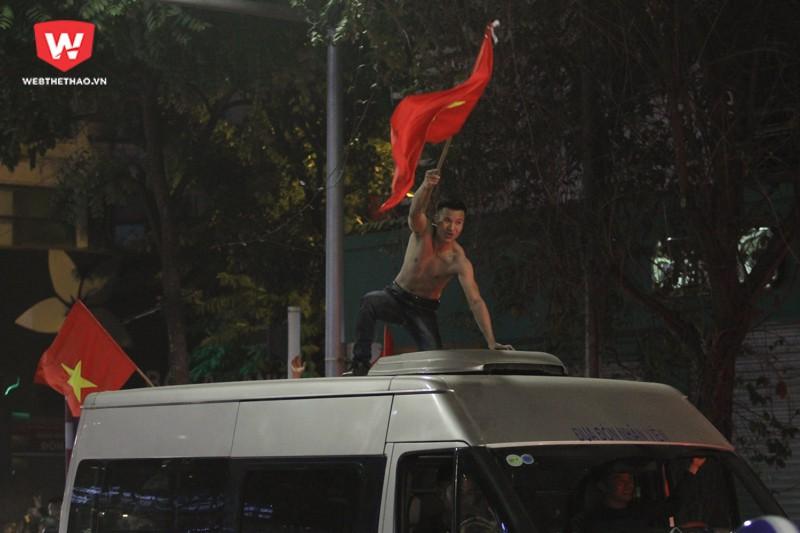 Có những thanh niên ưa mạo hiểm, đứng hẳn lên nóc xe ô tô để vẫy cờ ăn mừng. Hình ảnh: Trung Thu.