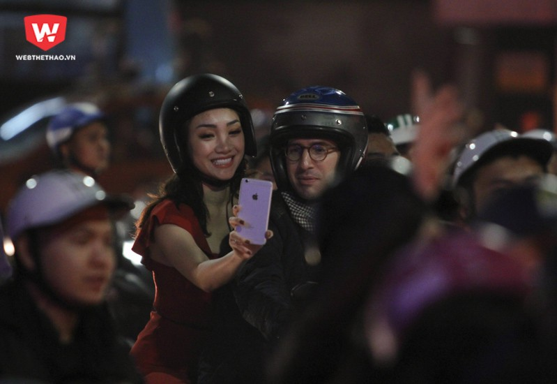 Một cặp đôi gái Việt, trai Tây tranh thủ lưu giữ lại khoảnh khắc giữa dòng xe cộ chật ních. Hình ảnh: Trung Thu.
