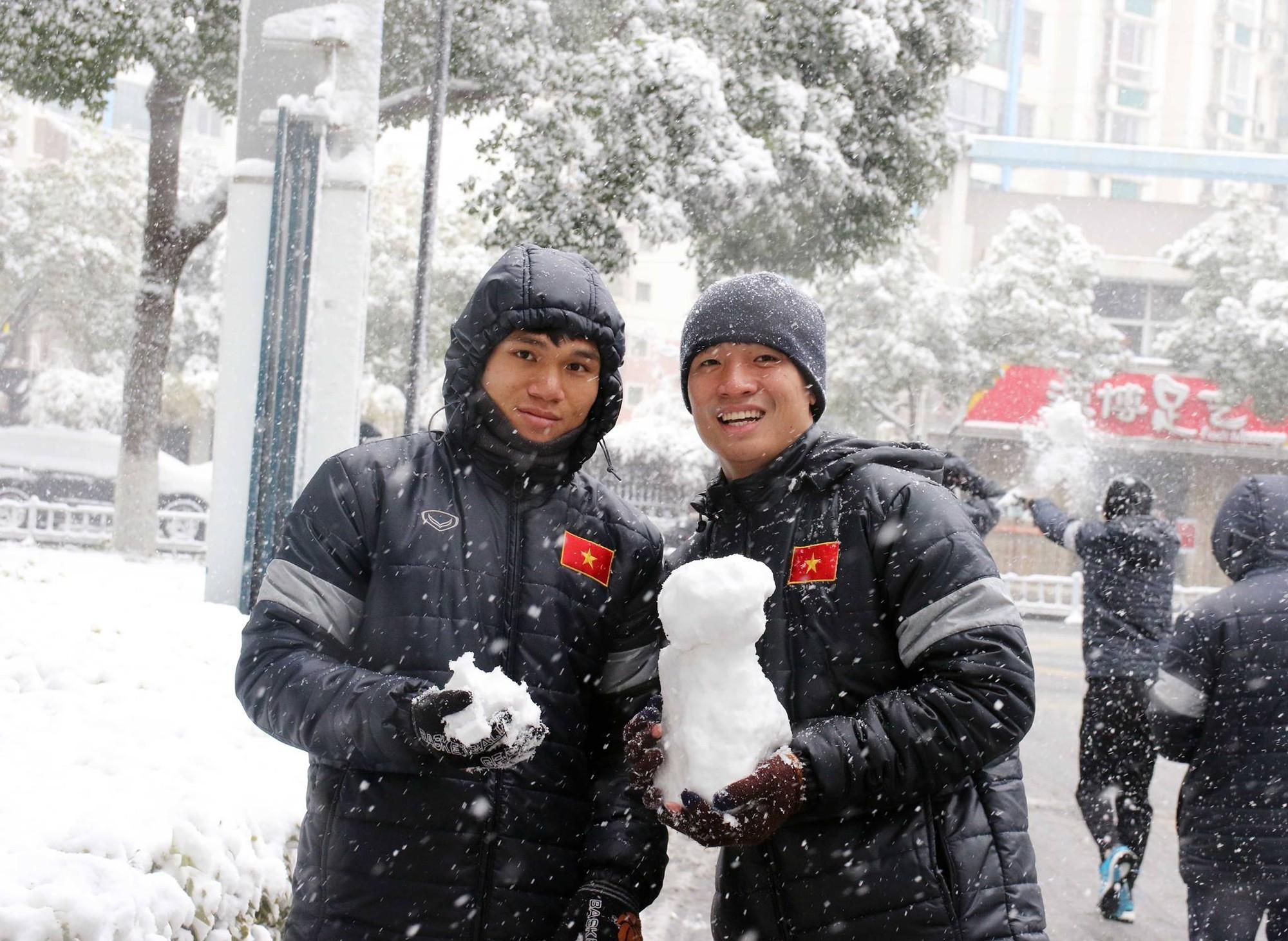 Nauyễn Xuân Mạnh và trung vệ Bùi Tiến Dũng ''cứng đơ'' bên ngoài khung cảnh tuyết rơi. Sáng nay, cả đội U23 Việt Nam được ra ngoài ngắm phố phường. Ảnh: VFF.