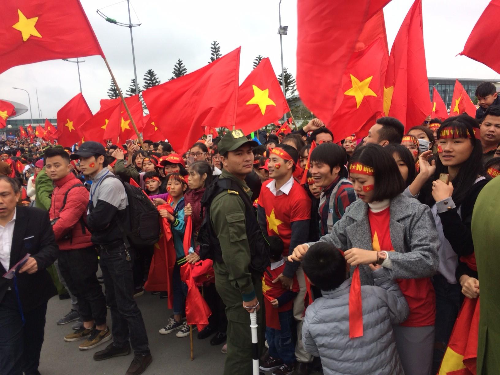 Rừng cờ đỏ sao vàng đang tung bay ngay tại lúc này ở sân bay Nội Bài. Chuyên cơ chở U23 Việt Nam đã bay đến thành phố Vũ Hán (Trung Quốc), dự kiến có mặt tại Hà Nội lúc 13h00. Ảnh: Hải Đăng.