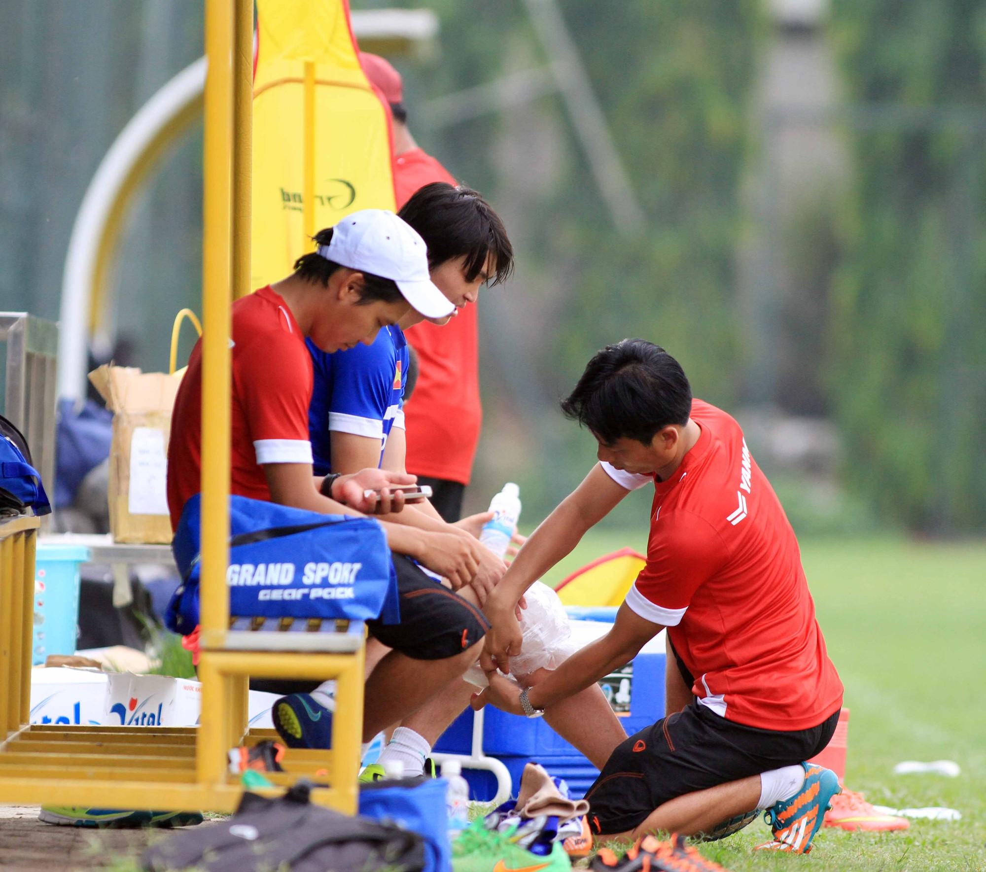 Bác sỹ Nguyễn Trọng Thùy (ngồi) dùng đá để chườm cho cầu thủ