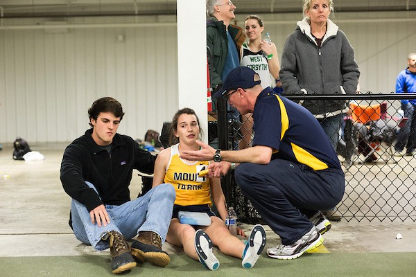 January 25, 2014. Winston Salem, North Carolina. After failing to make a personal best time in the 1600m race at the 2014 David Oliver Classic, Kayla Montgomery is comforted by her coach, Patrick Cromwell, right, and boyfriend Louis Pikula. Montgomery must ice down her legs after races, as they lose feeling and overheat due to the MS.   3 and a half years ago, during an examination after sustaining tailbone and head injuries from a fall during a soccer game, Kayla Montgomery, now 18, was diagnosed with multiple sclerosis. Montgomery, then a decent runner, refused to be limited by her diagnosis, and after years of training has become one of the best high school runners in the country.